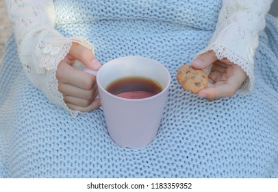 Hands of little girl in cozy hand warmers fingerless gloves holding cup of tea and cookie on her knees wrapped in warm knitted plaid. Hugge or lagom style.