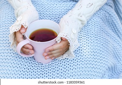 Hands of little girl in cozy hand warmers fingerless gloves holding cup of tea on her knees wrapped in warm knitted plaid. Hugge or lagom style. Cold season concept