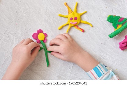 Hands of little girl making flower and sun and other  from colorful clay dough, plasticine, Home Education game with clay. Early development concept