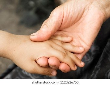 hands of a little girl and an old grandmother. Hands of a little kids holding elderly man, World Kindness Day concept and Adult day care center week