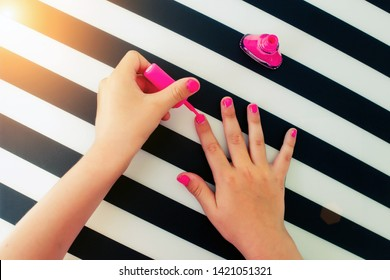 Hands of the little girl paint nails pink nail varnish on striped is black a white background. Top view