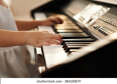 Hands of little girl playing piano, selective focus