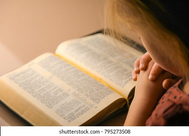 Hands of a little girl in prayer. The little girl prays in the evening. A girl with a bible.