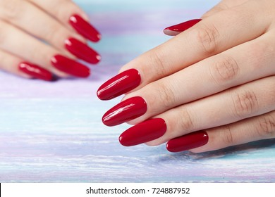 Hands with long artificial manicured nails colored with red nail polish