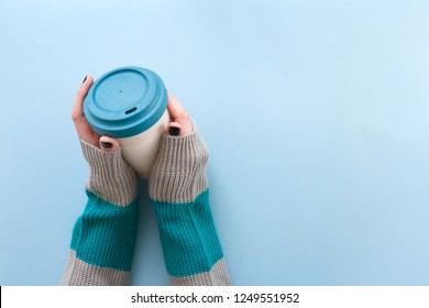 Hands in long sleeve knitted sweater, holding bamboo reusable cup with lid on, overhead on blue background.