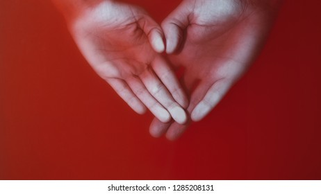 hands of a loving couple pressed with palms to glass in water on red background, man's and woman's hands in shape of heart, concept love and feelings, mysterious art,cover for novel