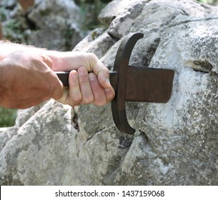 hands and the magical sword in the stone of King Arthur