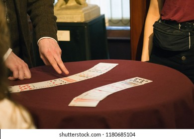 Hands of a magician displaying cards on a table, Edinburgh, Scotland.