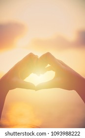 Hands make in heart form love with silhouette at sun set background