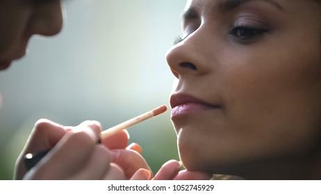 Hands of makeup artist applying lip gloss, preparing beautiful bride for wedding