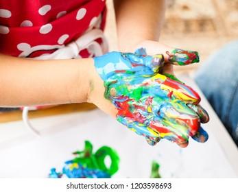 Hands making finger paint art at closeup