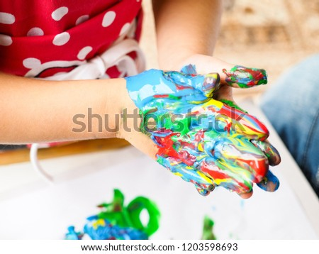 Hands making finger paint art at closeup