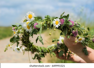 Hands making flower chain of chamomile and clover on sunny spring meadow with dirt road in the background.