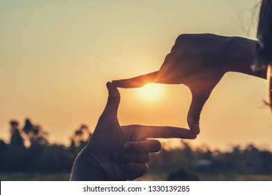 hands making framing view distant over sunset