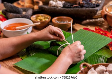 Hands making Guatemalan tamales.