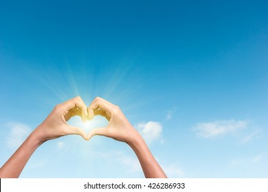 hands making a heart shape in the blue sky with sunlight