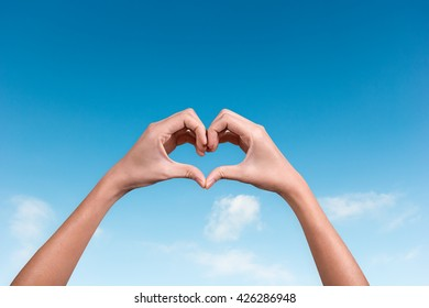 hands making a heart shape in the blue sky
