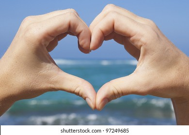 Hands Making Heart Shape with Ocean Background