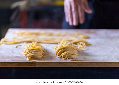 Hands making pasta on the table. Wheat flour spaghetti.  Italian pasta manufacture.  Chef making spaghetti in the kitchen. Traditional italian food