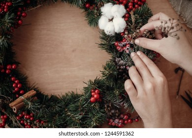 Hands making rustic christmas wreath, holding herbs at fir branches, red berries , pine cones, cotton on rustic wooden background. Atmospheric moody image at winter holiday workshop