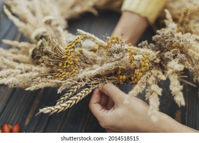 Hands making stylish autumn rustic wreath with dry grass, wildflowers and wheat on rustic wooden table in room. Fall holiday workshop. Florist making boho wreath on dark wood