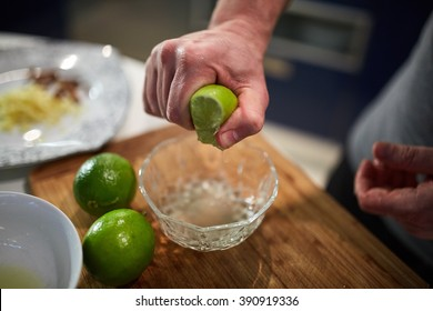 Hands of male chef squeezing limes in a bowl