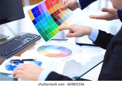 Hands of male designer in office working with colour samples. Businessman at workplace choosing colourful paper charts. Creative people or advertising business concept