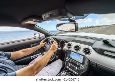 Hands of a male driver on a steering wheel driving through the mountains on a scenic California coast road