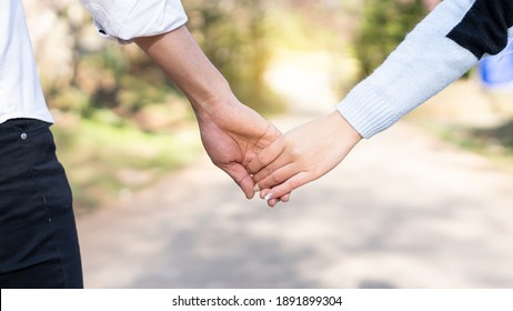 The hands of the male and female lovers who hold hands walk forward high with blurred background