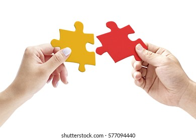 hands of a male and female putting together two matching jigsaw pieces, isolated on white background.