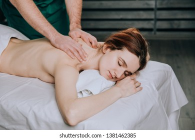 The hands of a male masseur doing massage shoulder of a young woman. Beautiful relaxed face of a young woman with brown hair and closed eyes.