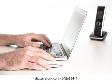 hands of a male person working on a notebook laptop computer and mouse on white desk surface