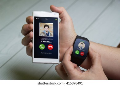 Hands male with smartwatch and smartphone with call on the screen. All graphics on the screen are made up.