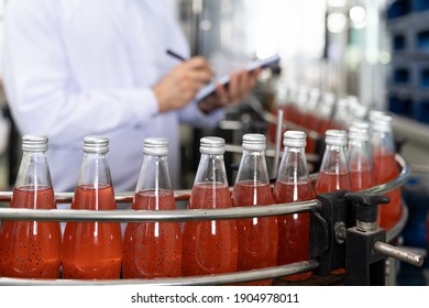 Hands of male worker writing notes about product of Basil seed with fruit on the conveyor belt in the beverage factory. Worker checking bottling line for processing. Inspection quality control
