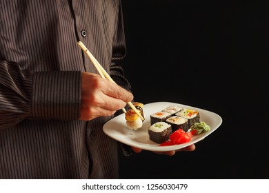 Hands of man in a black shirt with plate with sushi set on a black background