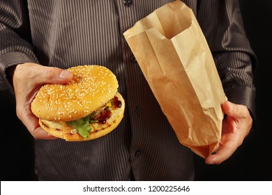 Hands of a man in a black shirt take out a hamburger from a one-time package on a black background