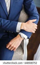 Hands of a man in a business suit, a man in a stylish blue suit and a white shirt, the hands of the groom with a watch, watch on a man's hand close-up
