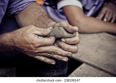 hands of a man, creating an earthen jar on the circle