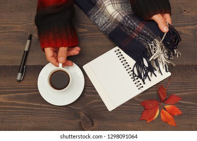 Hands of man with a cup of coffee and scarf at wooden table with a notebook and pen and autumn leaves