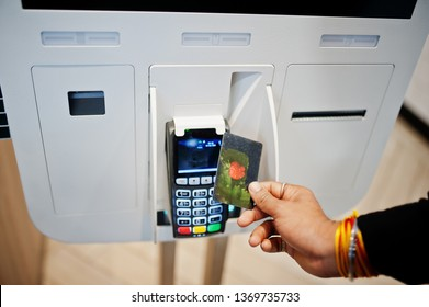 Hands of man customer at store place orders and pay by contactless credit card through self pay floor kiosk for fast food, payment terminal. Pay pass.