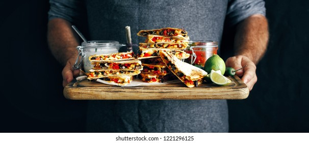 In the hands man cutting board with vegetarian snacks: quesadilla with vegetables and cheese on dark background