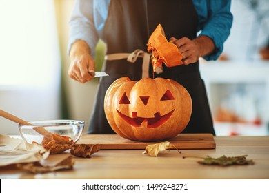 hands of   man cutting a pumpkin to halloween