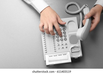 Hands of man dialing telephone number in office