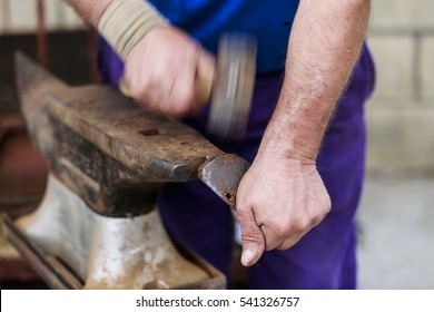 The hands of a man fixing the horseshoe of a horse