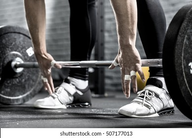 Hands of a man in front of the barbell on the background of his legs in the black pants and the white sneakers. Close-up horizontal photo.
