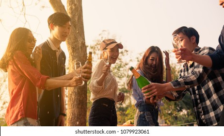 Hands of man in group of friends opening champange for celebrate