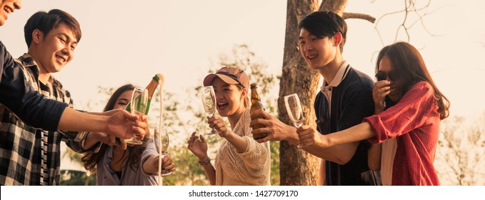 Hands of man in group of friends opening champagne for celebrate, cropped dimension for banner
