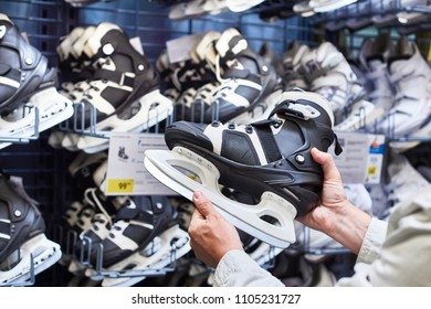 Hands of man with hockey skates in the sports shop