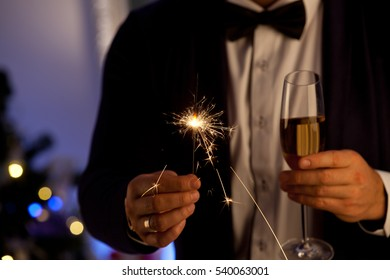Hands of man holding Bengal light at the party. Sparkler - New Year's Eve. Party, holidays, nightlife and people concept