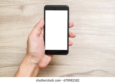 Hands of a man holding blank smart phone. He is looking a mobile phone on the desk and the desk is make by the wood.